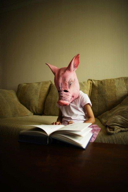 Girl in pig mask reads book Potbox.it
