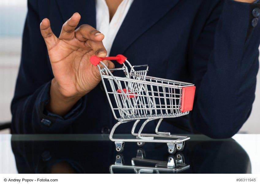 Close-up Of Businesswoman Holding Cart On Desk