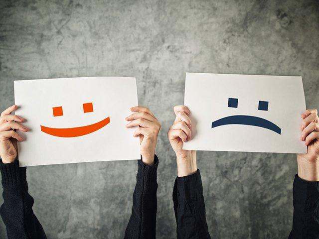 Happy and sad face. Women holding papers with happy and sad emoticons.