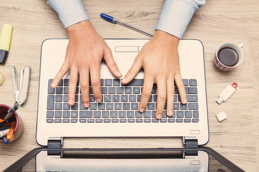 mani di uomo al alvoro sulla tastiera di un notebook informatico