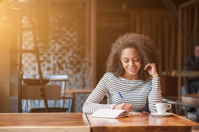 Attractive african girl is studying in cafeteria. She is making notes and smiling