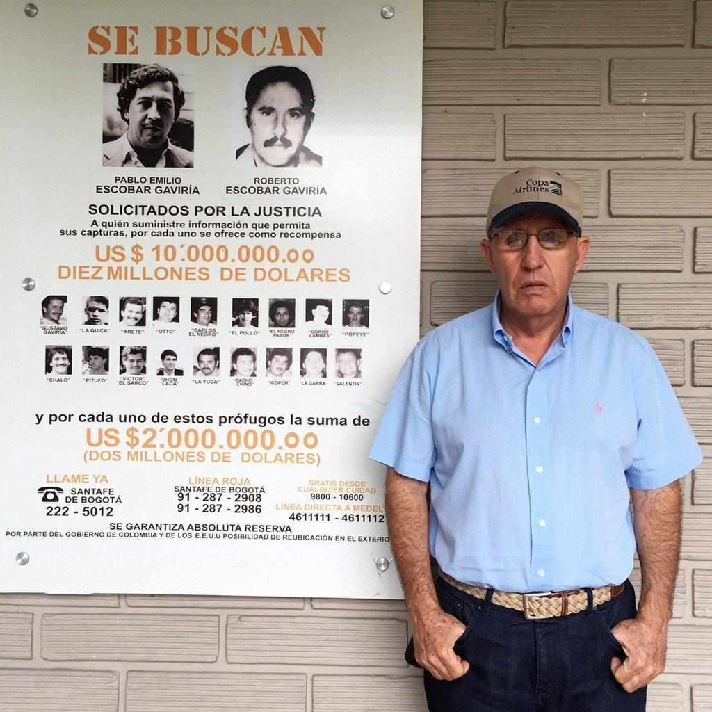 Roberto, fratello di Pablo, affianco ad un manifesto segnaletico che li riguarda