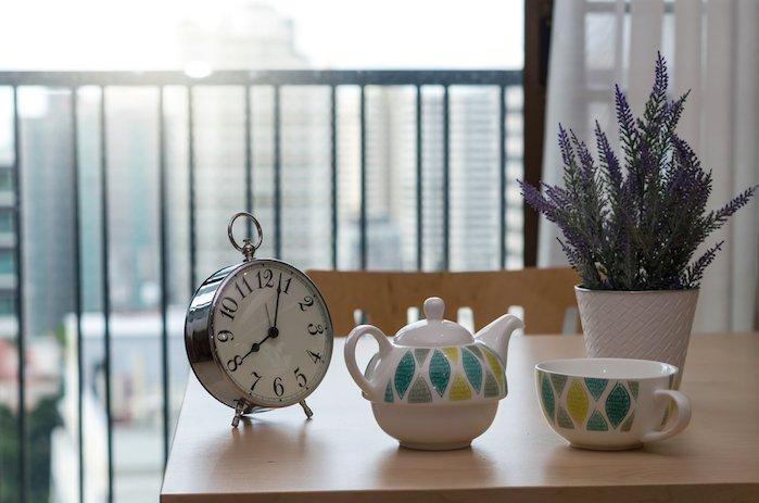 vintage clock on the wood table with tea cup at morning time at Luxury Interior kitchen room