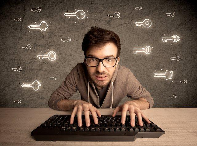 A young internet geek working online, hacking login passwords of social media users concept with glowing drawn keys on the wall