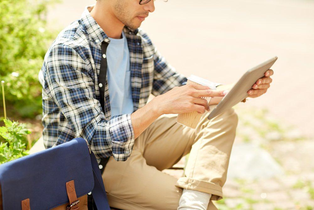business, education, technology, communication and people concept - close up of creative or hipster man with tablet pc computer drinking coffee from paper cup and sitting on city street bench