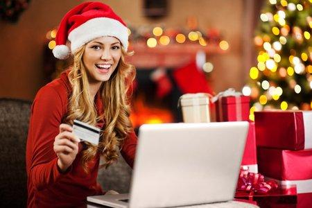 Cheerful young woman wearing Santa's hat is buying Christmas presents online.